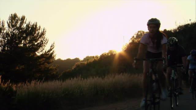 vídeos de stock, filmes e b-roll de medium shot backlit group of cyclists biking in a line / dusk - menos de 10 segundos
