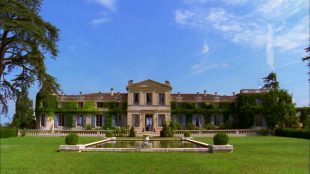 stockvideo's en b-roll-footage met medium shot backyard of chateau w/square fountain in lawn w/blue skies in background / france - landhuis