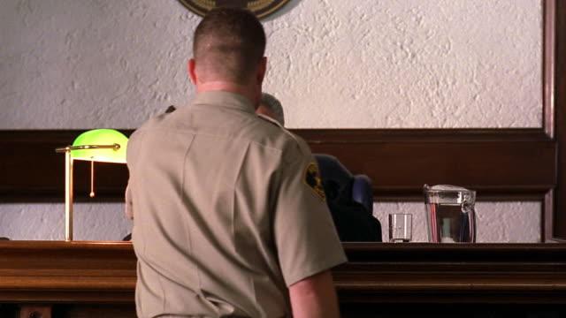 medium shot bailiff handing judge document / judge reading papers - giudice video stock e b–roll