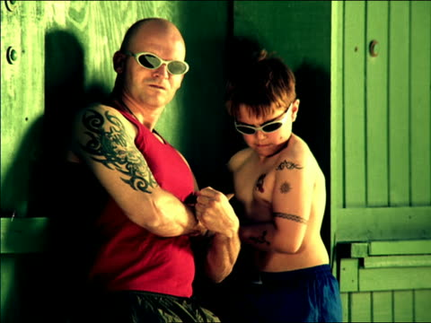 medium shot bald man and boy flexing arms with tattoos + wearing sunglasses / mexico city - copying stock videos & royalty-free footage