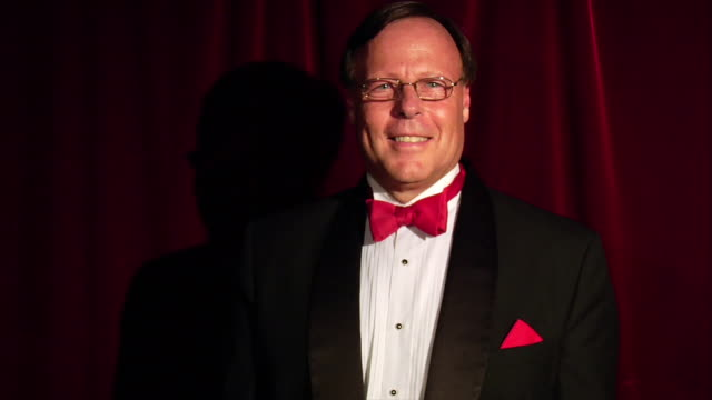 medium shot balding man in tuxedo with red tie standing in front of a red stage curtain, smiling - balding stock videos & royalty-free footage