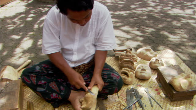 Medium shot Balinese mask maker Ida Bagus Anon carving mask in Ubud / Bali, Indonesia