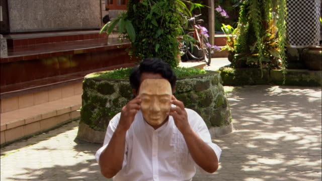 Medium shot Balinese mask maker Ida Bagus Anon holding up finished mask to his face in Ubud / Bali, Indonesia