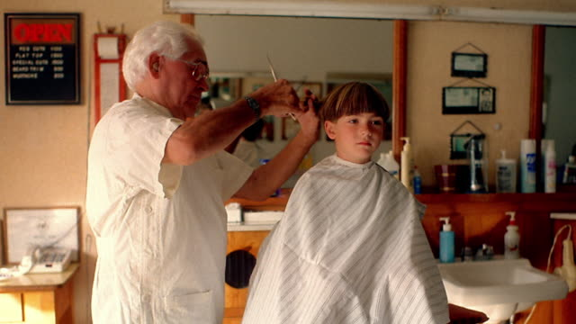 medium shot barber cutting boy's hair with comb and scissors in barber chair - barber chair stock videos & royalty-free footage