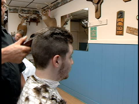medium shot barber cutting young man's hair - stoppelbart stock-videos und b-roll-filmmaterial