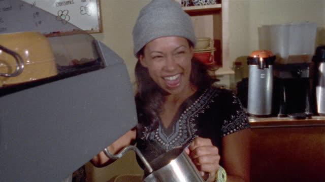 Medium shot barista laughing and talking as she steams milk