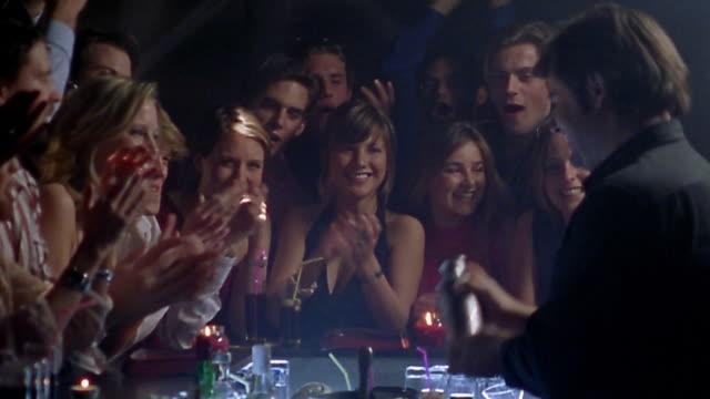 vidéos et rushes de medium shot bartender mixing drinks / customers applauding - shaker