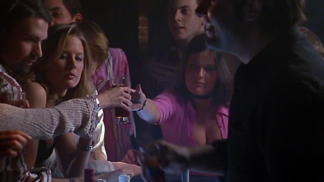 Medium shot bartender serving drinks at crowded bar