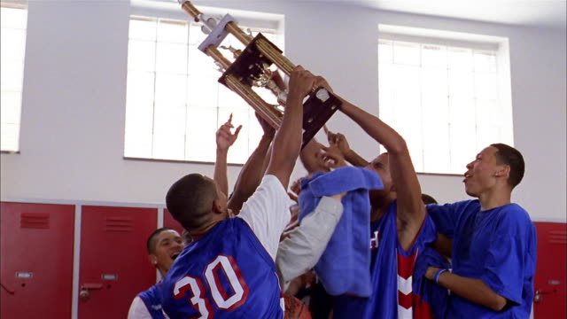 Medium shot basketball players raising trophy and cheering in locker room