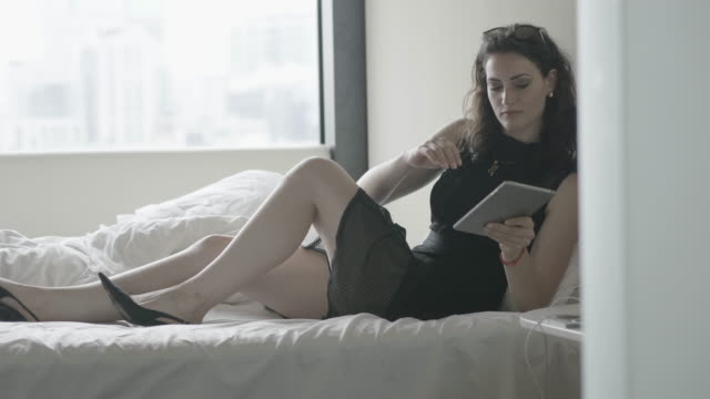 medium shot, beautiful woman in black dress uses tablet in hotel - black dress stock videos & royalty-free footage