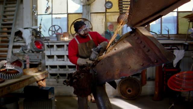 vídeos de stock e filmes b-roll de medium shot black artist w/goggles sanding metal sculpture in studio w/sparks flying off - escultura