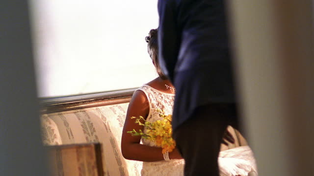 vídeos de stock e filmes b-roll de medium shot black bride and black middle aged man sitting down / man advising bride - pai da noiva