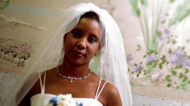 vídeos de stock, filmes e b-roll de medium shot black bride holding bouquet and smiling - bouquet