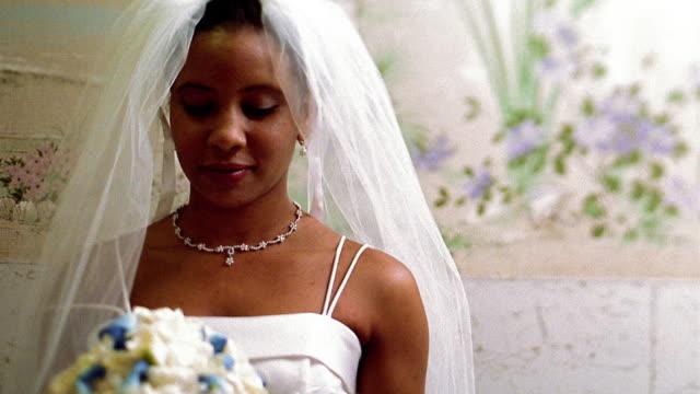 Medium shot Black bride holding bouquet