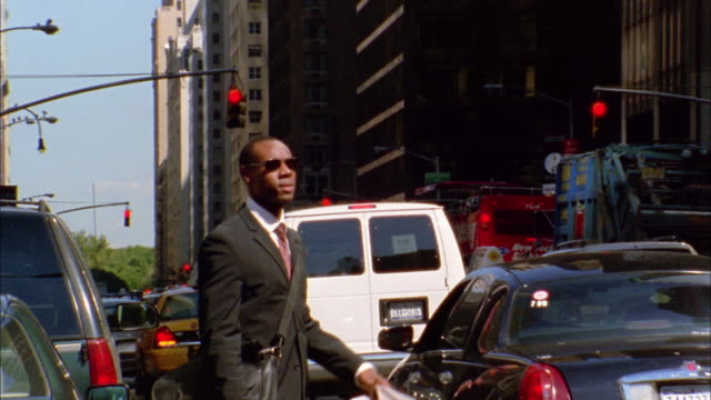 Medium shot Black businessman trying to hail taxicab / NYC