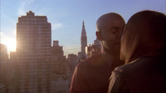 Medium shot Black couple hugging on rooftop in midtown Manhattan / NYC
