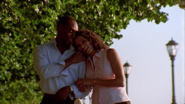 Medium shot Black couple walking arm-in-arm outdoors