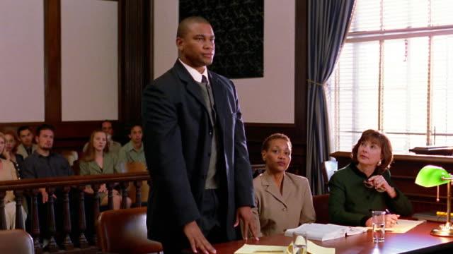 vídeos de stock e filmes b-roll de medium shot black male lawyer standing and objecting / lawyers + plaintiff conferring - sala de tribunal