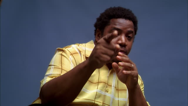 vídeos y material grabado en eventos de stock de medium shot black man in yellow shirt looking at cam and pointing against blue background - indicar