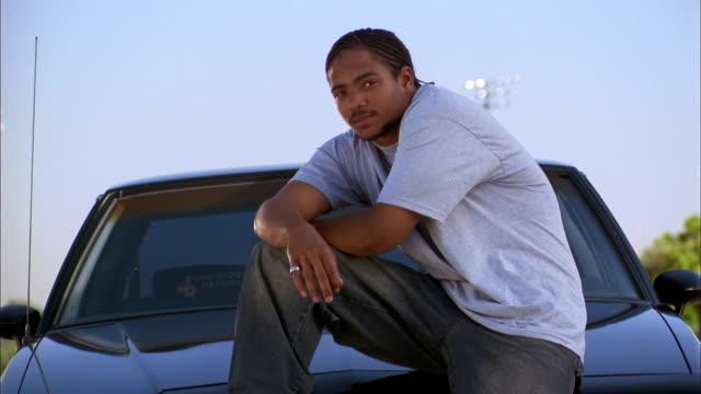 Medium shot Black man posing w/leg on car hood and looking at CAM