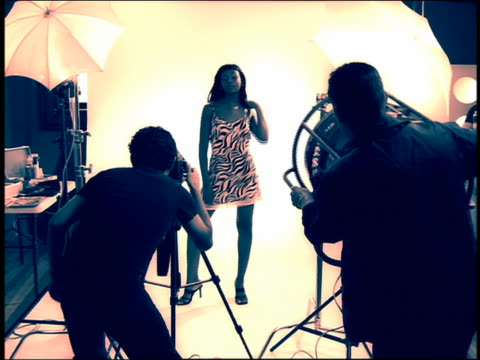 Medium shot Black model posing in studio for photographer and fan operator in foreground