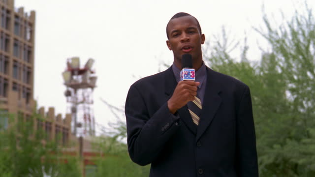 Medium shot Black television reporter raising microphone to mouth and talking outdoors