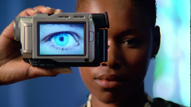 Medium shot Black woman holding up digital camera with human eye image on screen