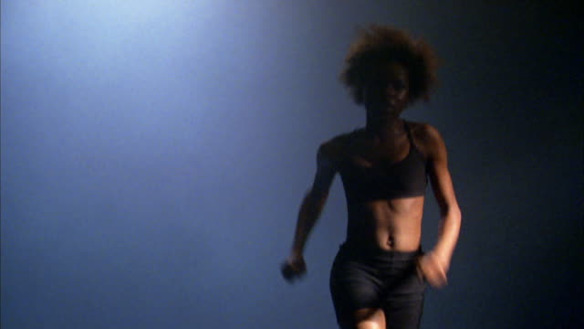 medium shot black woman running in place against blue background - belly button stock videos & royalty-free footage