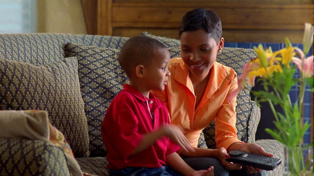 vídeos y material grabado en eventos de stock de medium shot black woman sitting on sofa with young boy and using remote control - encuadre de tres cuartos