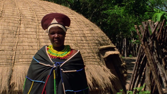 medium shot black zulu woman in native dress in front of hut / durban, kwazulu-natal, south africa - durban stock videos and b-roll footage