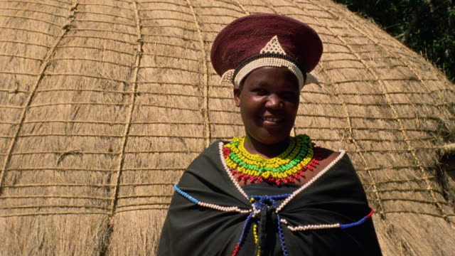medium shot black zulu woman in native dress in front of hut / durban, kwazulu-natal, south africa - grass hut stock videos & royalty-free footage