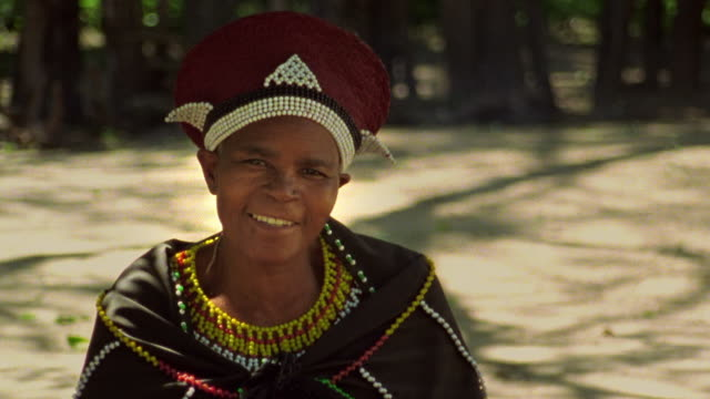 Medium shot Black Zulu woman in native dress smiling outdoors / Durban, KwaZulu-Natal, South Africa
