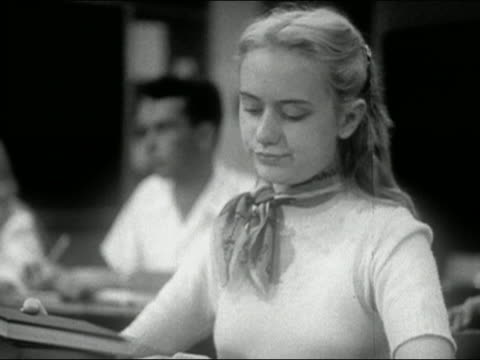 1954 medium shot blonde girl sitting at desk in classroom opens book and looks bored / audio - 1954 stock videos and b-roll footage