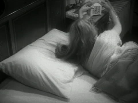 1954 medium shot blonde teenage girl in bed turning off alarm and going back to sleep / audio - napping stock-videos und b-roll-filmmaterial