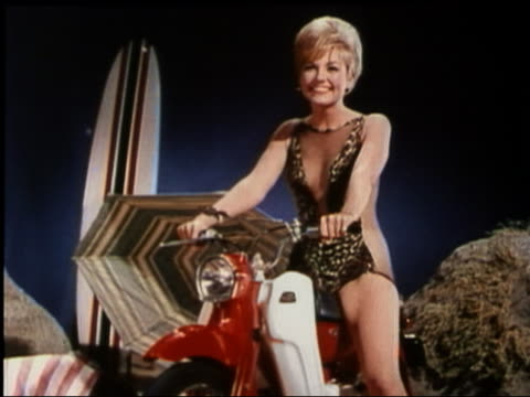 1965 medium shot blonde woman in swimsuit doing leg lifts on moped and smiling at CAM / 'Beach Blanket Bingo'