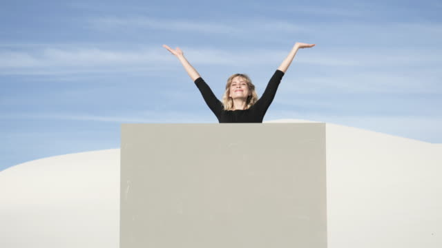 medium shot, blonde woman jumps out of grey portal in desert - peeking stock videos & royalty-free footage