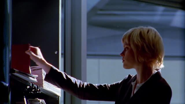 medium shot blonde woman lifting book off shelf / opening book / walking away - avvocato video stock e b–roll