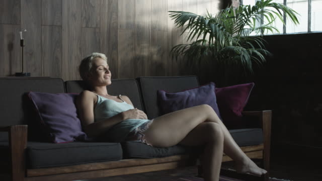 medium shot, blonde woman on apartment couch - kamisol stock-videos und b-roll-filmmaterial
