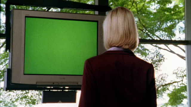 medium shot blonde woman watching blank tv monitor turning and looking at cam - television chroma key stock videos & royalty-free footage