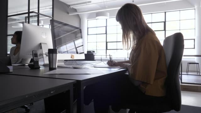 stockvideo's en b-roll-footage met medium shot, blonde woman works at computer - bureaustoel
