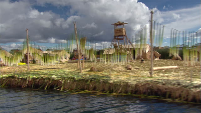 medium shot boat point of view along lake titicaca of island and structures created from totora reeds / reeds drying on lines / puno, peru - 草葺小屋点の映像素材/bロール