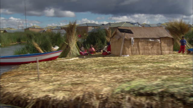 Medium shot boat point of view along Lake Titicaca of island created from totora reeds / Uros people gathered around huts in rural village / Puno, Peru
