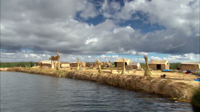 medium shot boat point of view along lake titicaca of island created from totora reeds / large swan-shaped structure / puno, peru - 草葺小屋点の映像素材/bロール