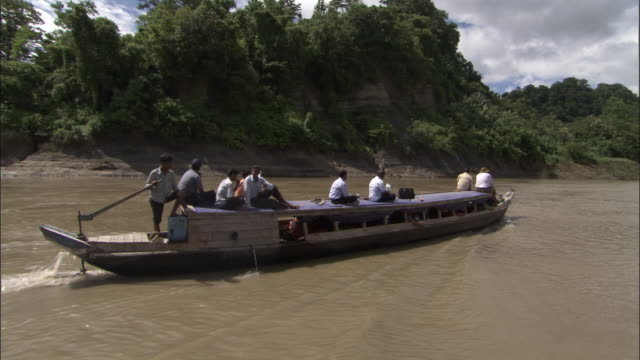 Medium Shot - Boat with several men on roof glides down river / Bangladesh
