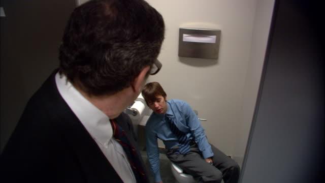 medium shot boss opening door of bathroom stall / male employee sleeping on toilet / boss walking away / low angle - public restroom stock videos and b-roll footage