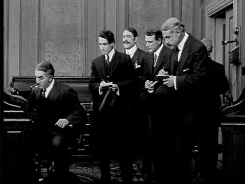 1909 b/w medium shot boss sits at desk as men wait for orders/ boss gives orders to men, who exit one by one/ boss running out door - 無声映画点の映像素材/bロール