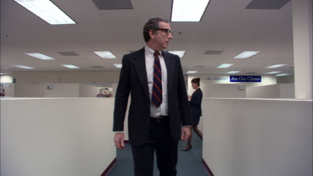 stockvideo's en b-roll-footage met medium shot boss walking through office and looking exasperated / female employee walking by + waving / low angle - verwarring