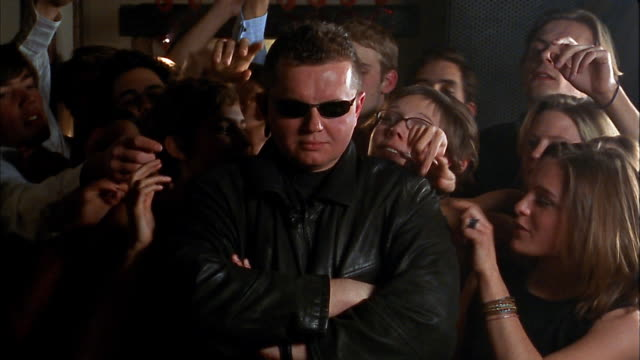 Medium shot bouncer in leather jacket and sunglasses standing with arms crossed / crowd in background