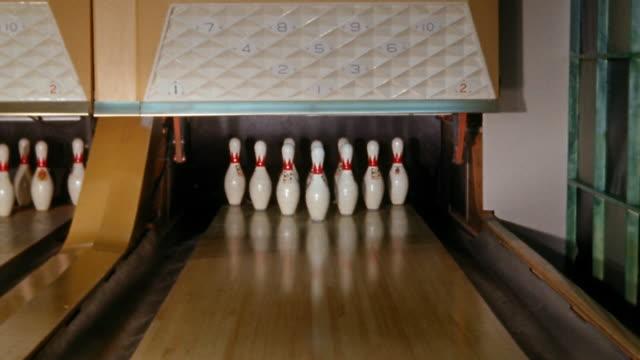 vídeos de stock, filmes e b-roll de medium shot bowling ball knocking down ten pins on alley for a strike - cancha de jogo de boliche