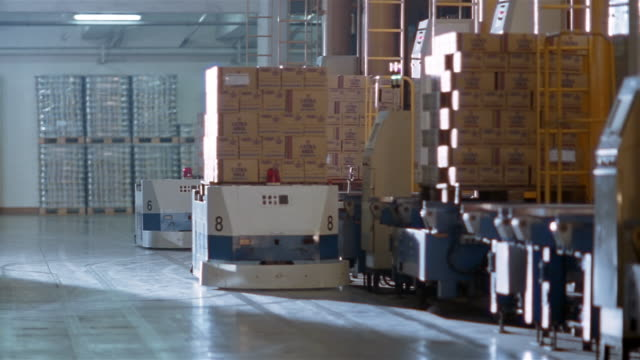 medium shot boxes being loaded onto robotic pallets at warehouse in milk factory - milk box stock videos & royalty-free footage